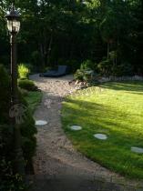 W tle pięknego ogrodu wypoczynkowy leżak składany Daytona