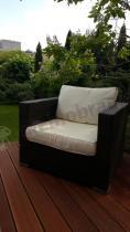 Wygodny fotel rattan effect Nilamito z brązowej plecionki i z jasnymi poduszkami