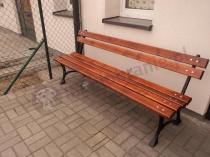 Żeliwna ławka o długości 180 cm na kostce w pobliżu domu