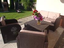 Zestaw mebli na taras ozdobiony wazonem pełnym kwiatów