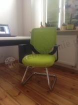 Zielony fotel na płozie Mobi skid na drewnianej podłodze