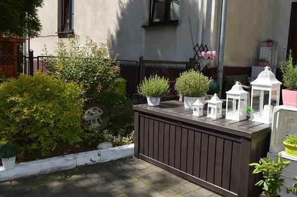 Skrzynia do ogrodu uzupełniona białymi latarenkami
