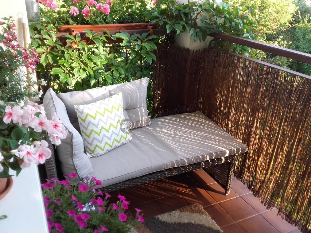 Sofa ogrodowa technorattan na balkon otoczona kwiatami