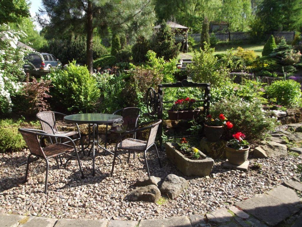 Stół z krzesłami ogrodowy ustawiony pośród bujnej zieleni