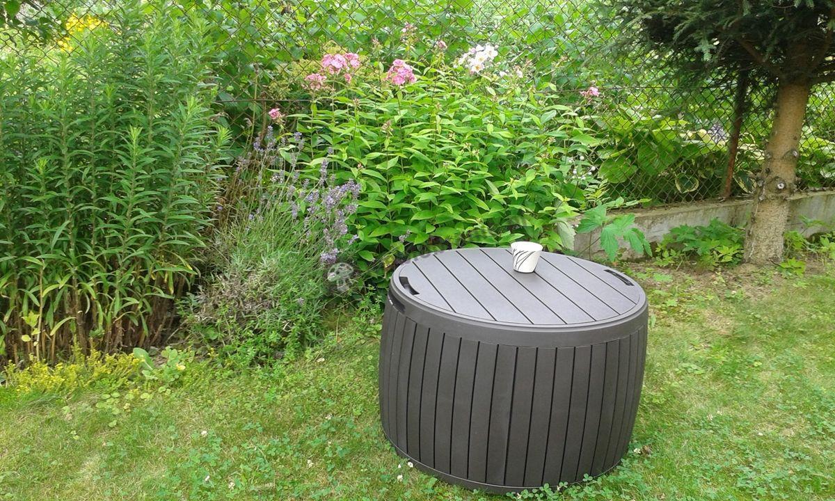 Stolik skrzynia ustawiony w rozkwieconym ogrodzie