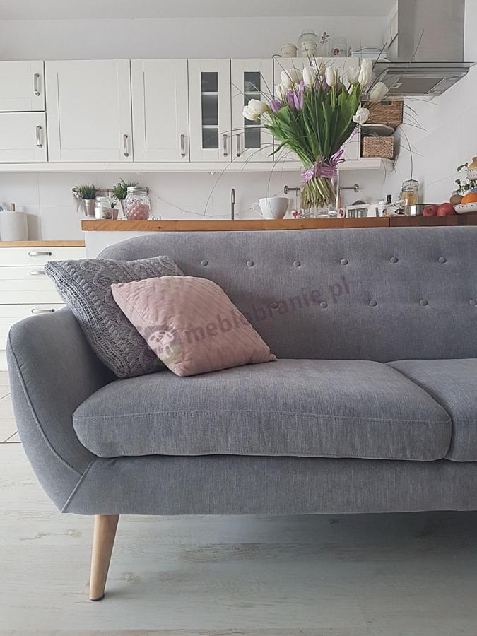 Szara nowoczesna sofa pikowana ozdobiona dekoracyjnymi poduszkami