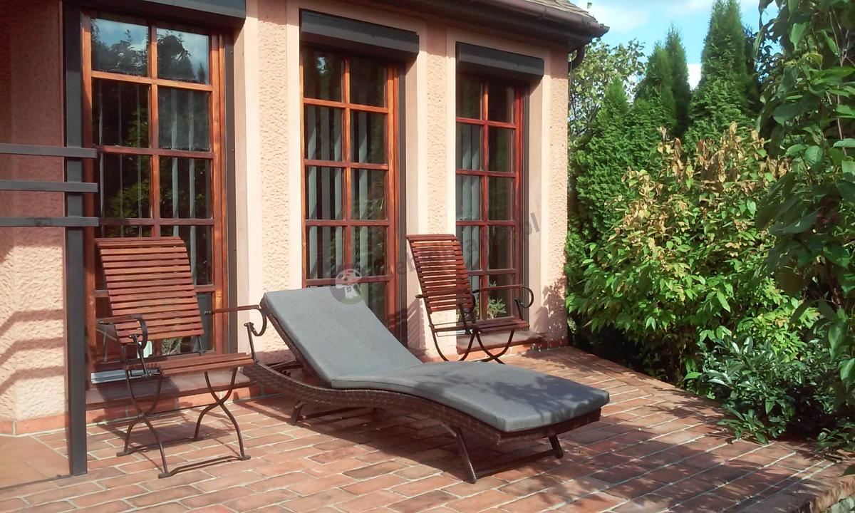 Leżak tarasowy Nilamito uzupełniony żeliwnymi krzesełkami