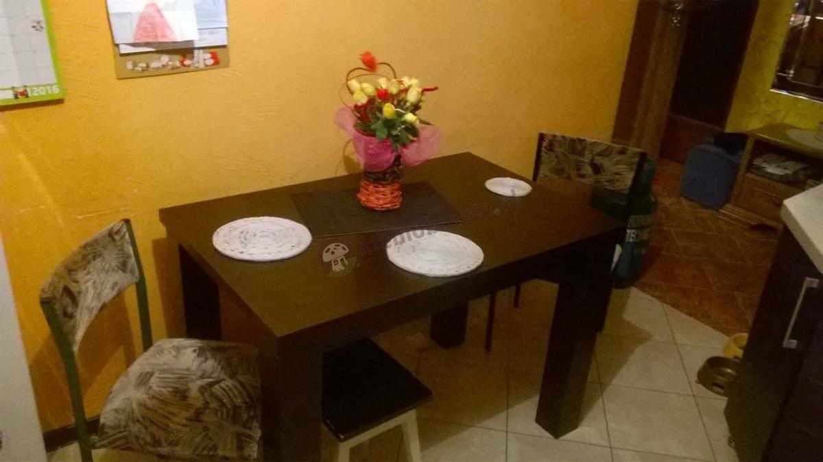 Wysoki stół do kuchni ustawiony przy ścianie