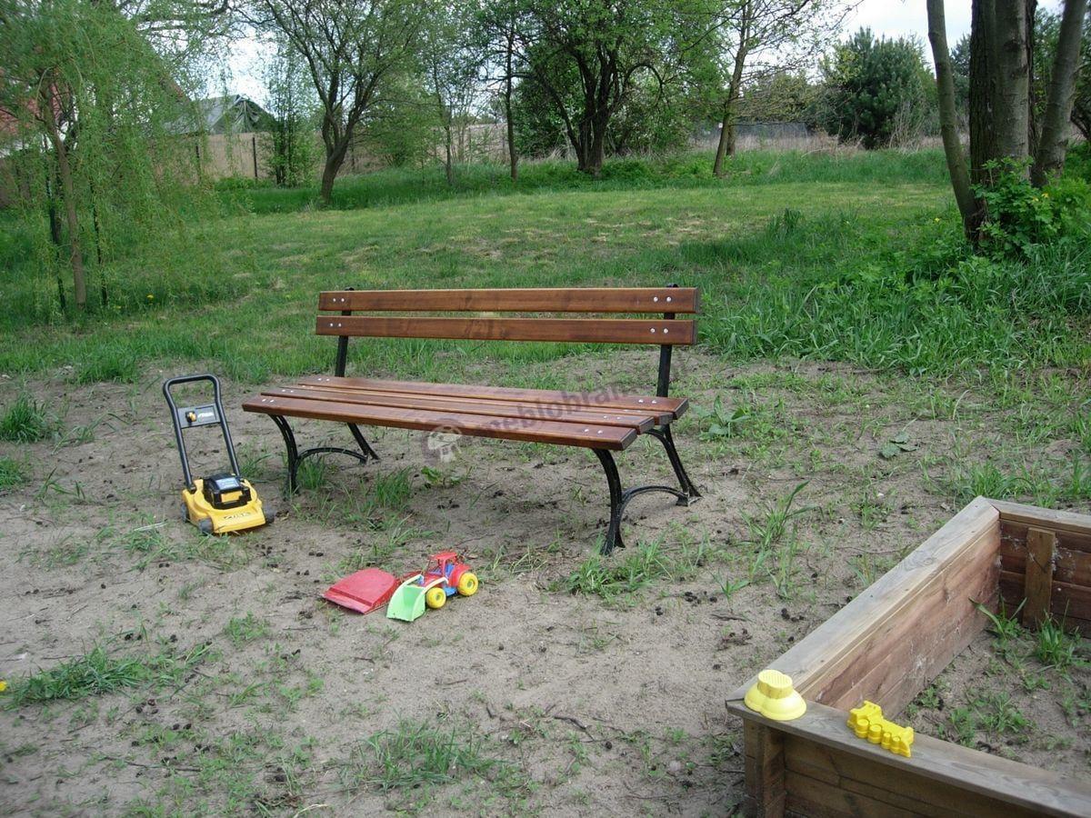 Żeliwna ławka ogrodowa używana przy piaskownicy