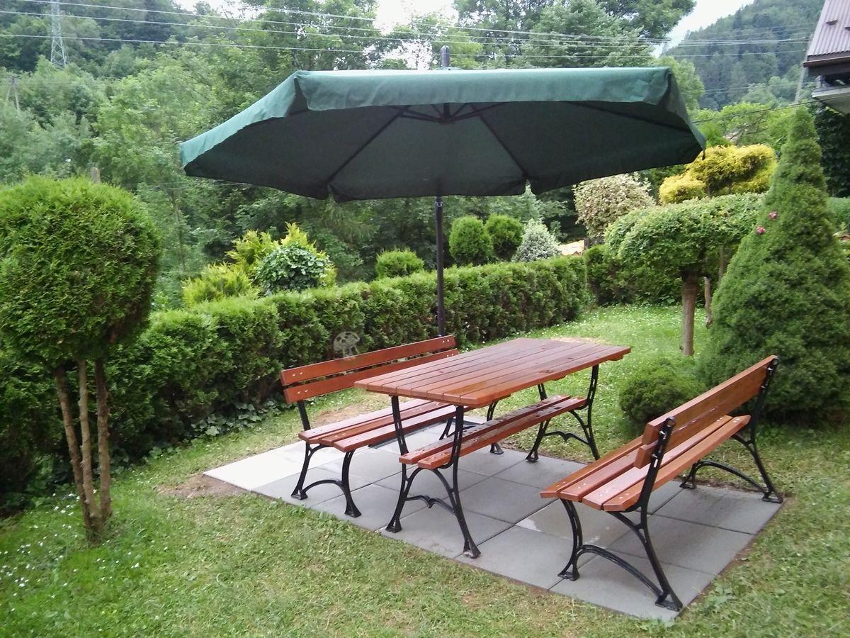 Żeliwny zestaw ogrodowy osłonięty dużym parasolem