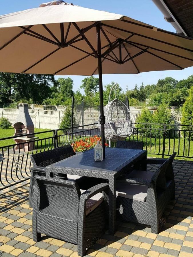 Zestaw Corfu Set z parasolem w przestrzennym nasłonecznionym ogrodzie