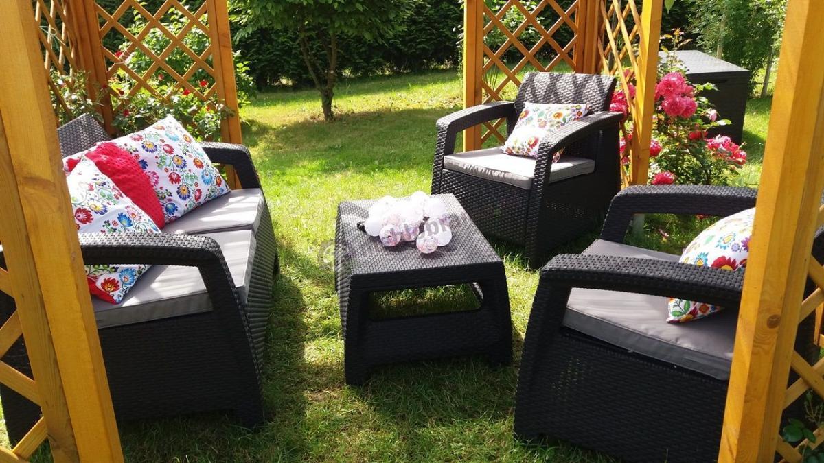 Zestaw mebli ogrodowych Corfu Curver w nasłonecznionym dużym ogrodzie z pięknymi poduchami