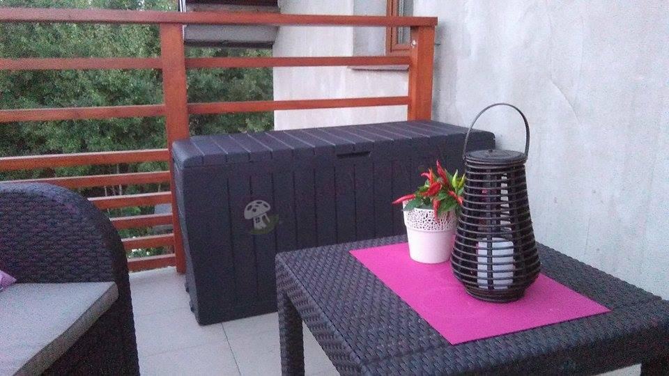 Zestaw wypoczynkowy uzupełniony skrzynią ogrodową używany na balkonie