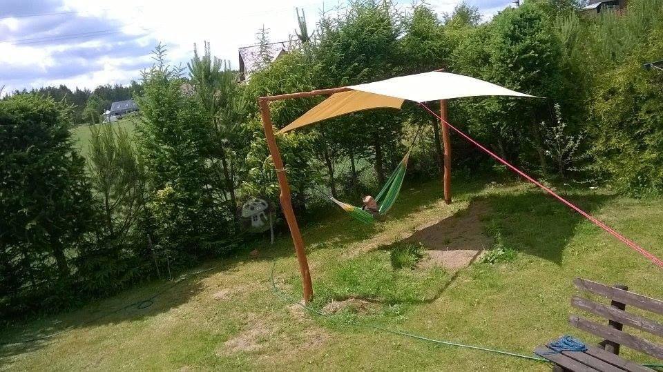 Zielony hamak ogrodowy pod osłoną przeciwsłoneczną